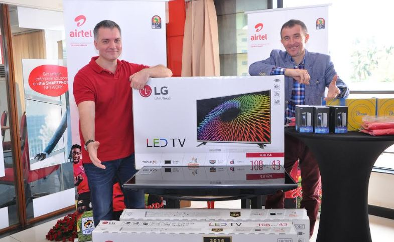 Airtel Uganda Managing Director, Anwar Soussa and Uganda Cranes head coach Milutin Micho Sredojevic pose alongside some of the goodies that will be won by subscribers who take part in the Tulumbe AFCON campaign.