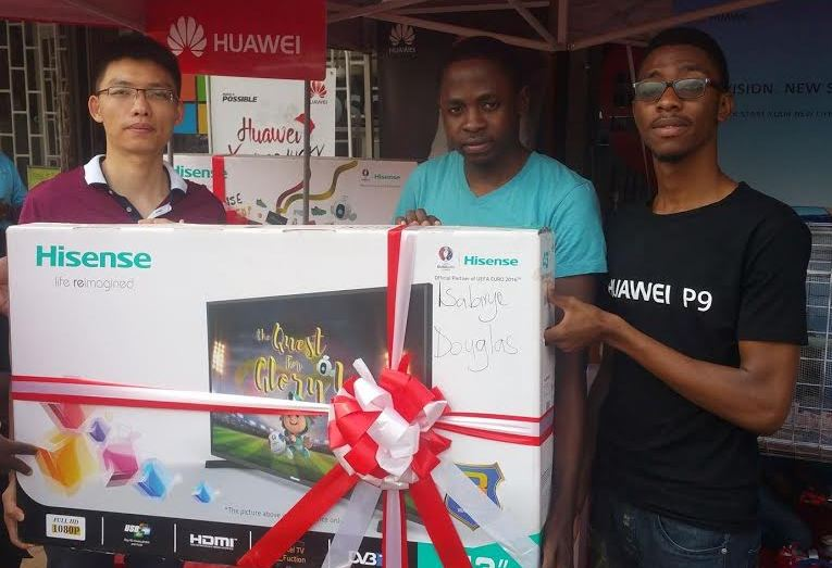 Isabirye Douglas(C) receives the 43' LED FHD Hisense TV screen that he won in a raffle draw from Zoey Dong Chegzu (L), Retail Manager, Huawei Uganda at Simba Telecom.