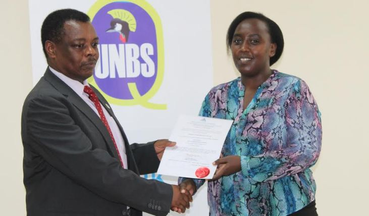 The Quality Manager of Uganda Industrial Research Institute Jean Rubakuba(left) receives a certificate of recognition from UNBS Executive Director Ben Manyindo.