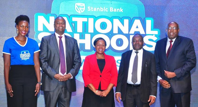 The Commissioner for Secondary Education Benson Kule (2nd Right) poses for a group photo with the Chairman Board of Directors Stanbic Bank Japheth Katto (Right), Stanbic CE Patrick Mweheire (2nd Left), KCCA Director Education Juliet Namuddu (centre) and Stanbic's Head Communication & CSI Cathy Adengo, (Right) during the launch of the Stanbic National Schools Championship.