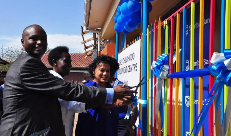 Stanbic Bank Uganda Chief Executive Patrick Mweheire (1st left) Stanbic Non – Executive Director Ruth Emuu (center), and the Chairperson Ka Tutandike Trust UK Anisha Rajapakse cut a ribbon during the official opening of the Ggaba Market Early Childhood Development (ECD) Centre in Bunga.