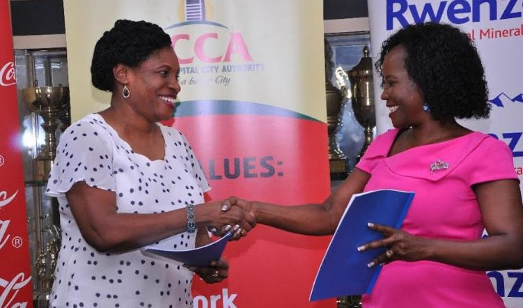 Coca-Cola Beverages Africa, The Group Director Public Affairs and Communications, Norah Odwesso and KCCA Executive Director Jennifer Musisi exchange the the signed MOU at KCCA officies.