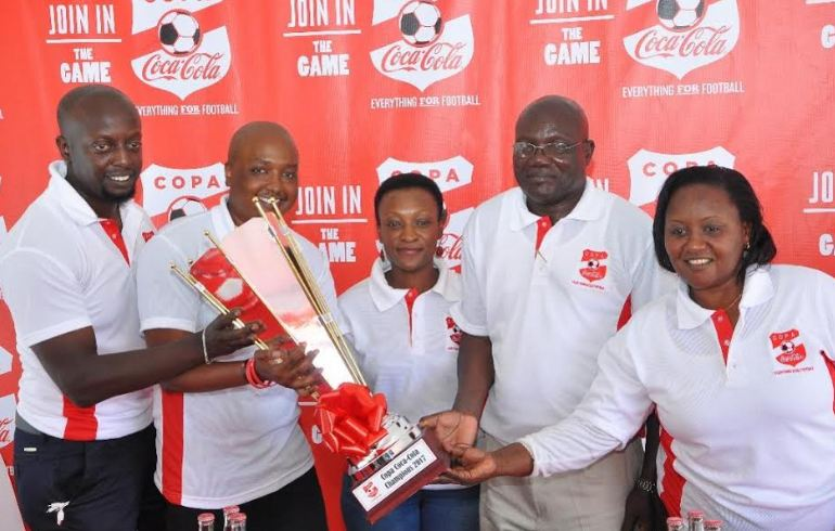 oca-Cola's Rodney Nzioka,(2nd left) and other officials display the Copa coca-cola 2017 edition trophy to media during a press conference.