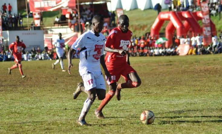 Masaka SS player takes on Yale SS player during the Copa Coca-Cola tournament kick-off