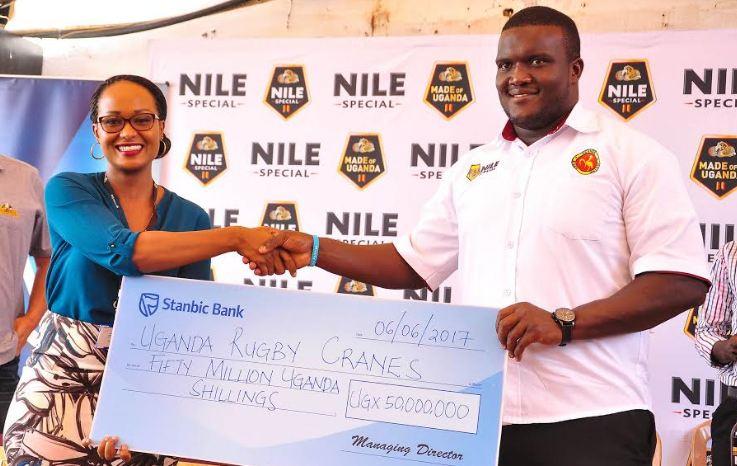 Stanbic Senior Marketing Manager Sonia Karamagi hands over a cheque worth Ugx 50 million to Uganda Rugby Cranes Captain Brian Odongo.
