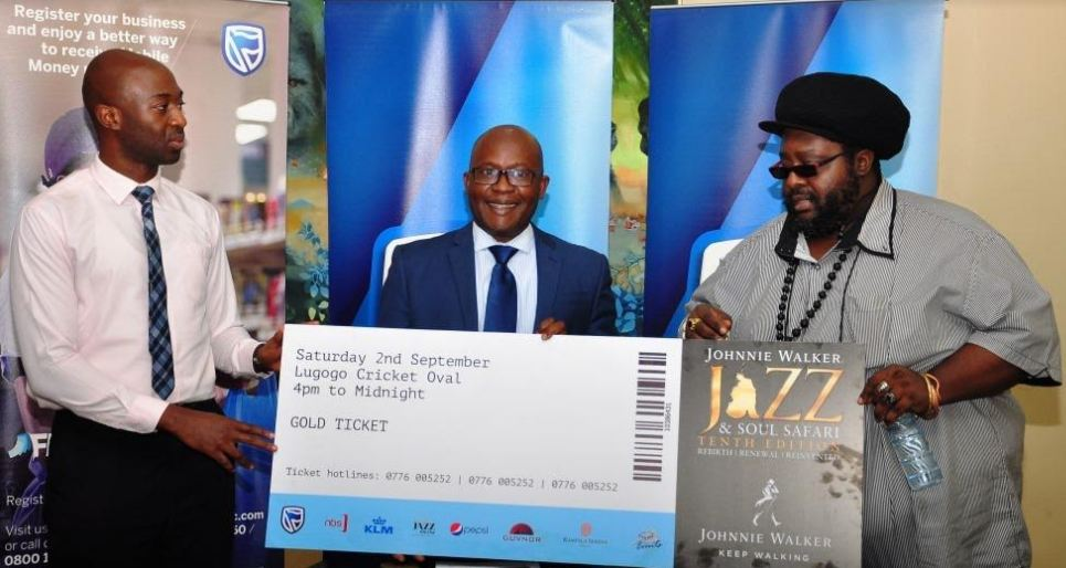 Stanbic Bank's Head Marketing and Communications, Daniel Ogong (C) and Product Manager CIB, Ivan Christian Kanyali (L) together with Tshaka Mayanja co-founder Jazz Safari display the Jazz and Soul Safari concert Gold Ticket.