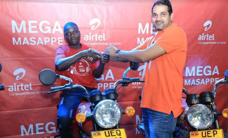 Airtel Uganda Marketing Director,Indrajeet Singh handing over motor bike keys to one of the winners in the Mega Masappe draw.