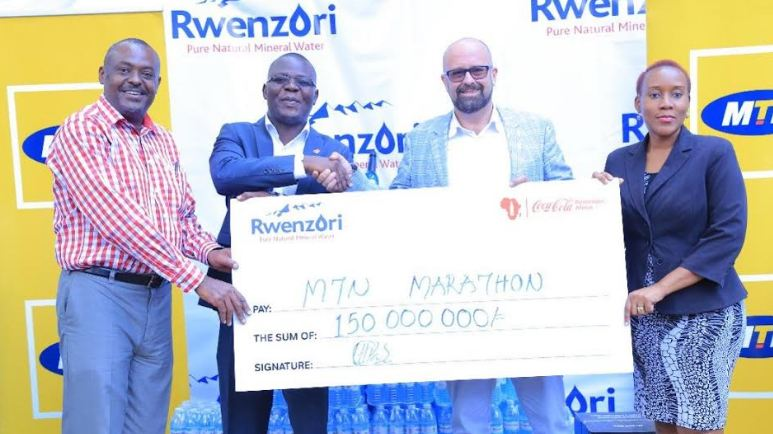 CCBA Public Relations and Communications director, Simon Kaheru, CCBA commercial director Patrick Oyuru, MTN's Chief Marketing Officer Olivier Prentnot pose with a dummy cheque during the announcement of the contribution towards the MTN Marathon.