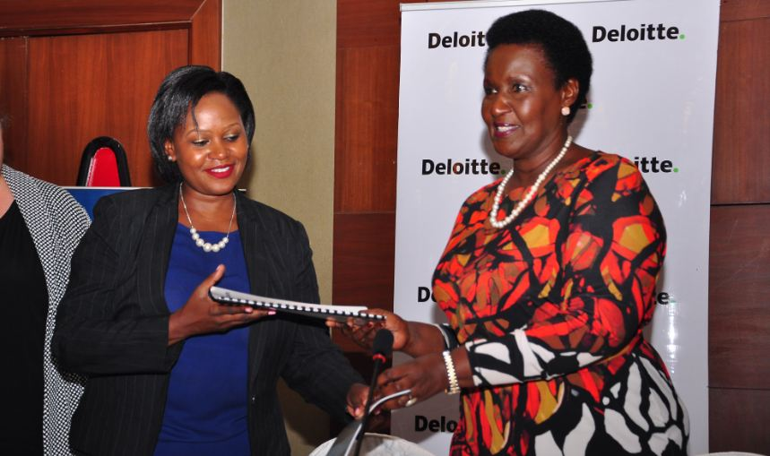 Deloitte Advisory Leader Mabel Ndawula and Minister of Trade, Industry and Cooperatives Amelia Kyambadde sign an MoU.