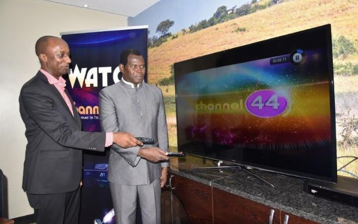 Charles Hamya (L) General Manager MultiChoice Uganda and Pastor Robert Kayanja tune in to Channel 44 on DStv during the launch ceremony