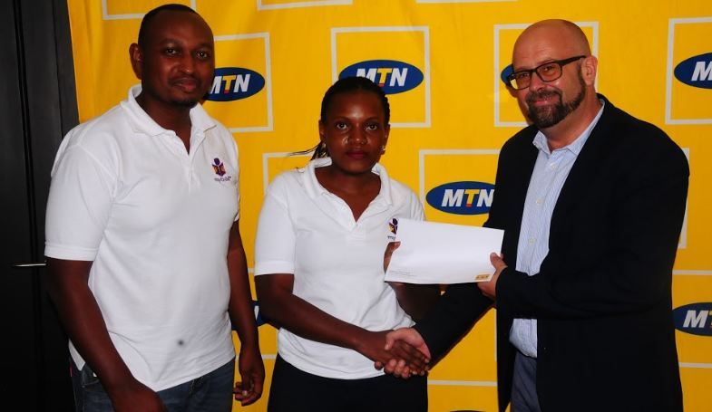 Best Education Application team, Ronald Sebuhinja and Nakyejjwe Allen receive their cash prize from MTN CMO, Olivier Prentout