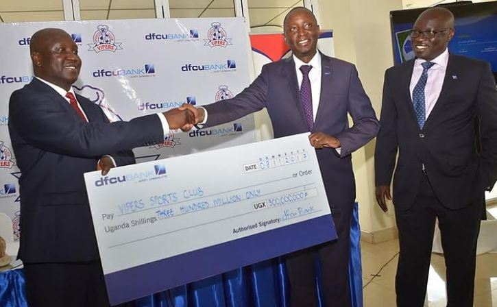 Vipers SC President Lawrence Mulindwa (L) and dfcu Bank's Chief of Business and Executive Director, Mr. William Sekabembe shake hands after signing the deal.