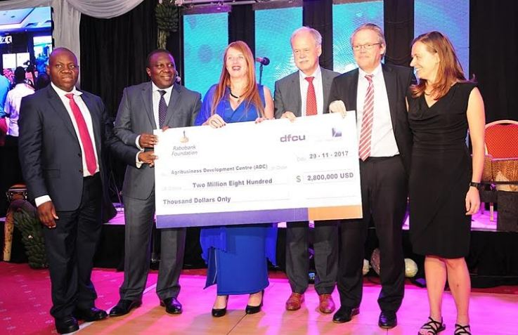 dfcu Bank board members with Agribusiness Development Centre and Rabobank Foundation executives show off the $2.8 million cheque for the ADC.