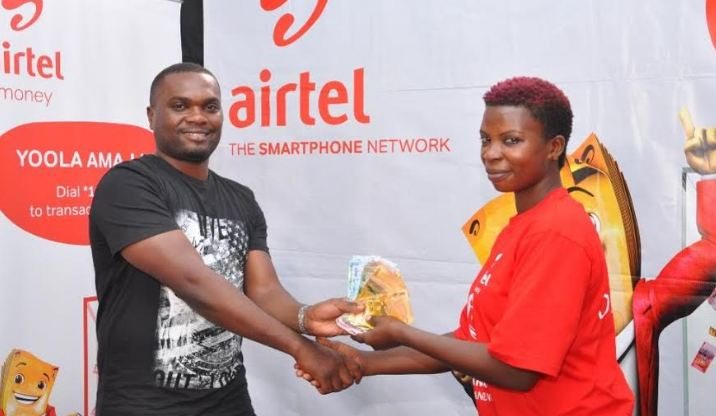 Namutebi Jane receiving money from Commercial Manager Airtel Money Morris Seguya