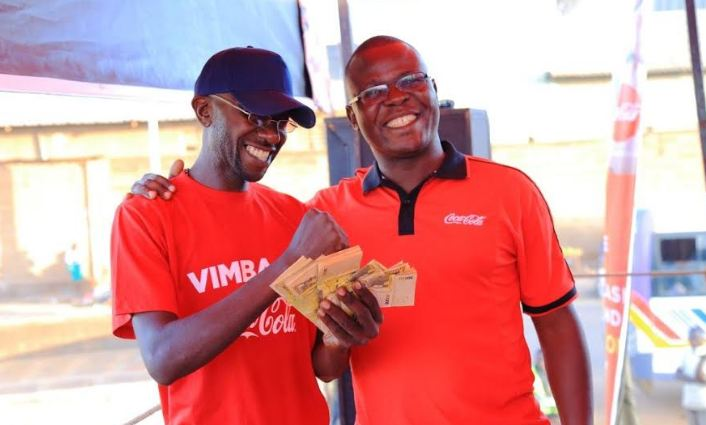 Paul Ofwono receives UGX5,000,000 from Cola's Patrick Oyuru at Kawempe