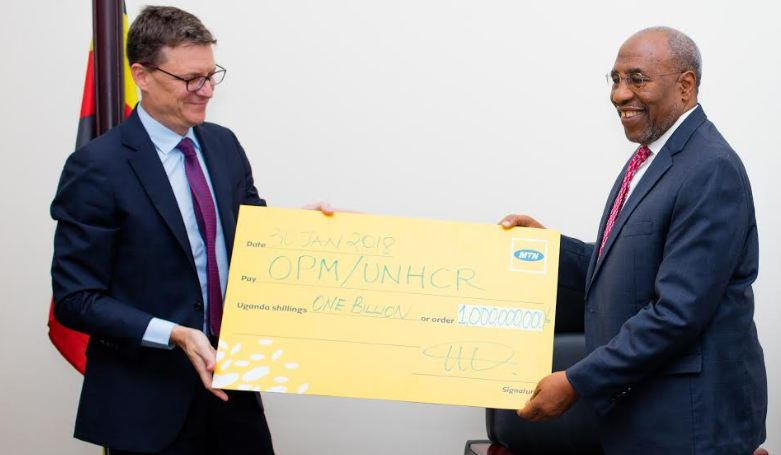 Mr. Rob Shuter, MTN Group President and CEO, hands over MTN Uganda's contribution of UGX 1billion that will go towards management of the Refugee Crisis in Uganda to Rt. Hon. Dr. Ruhakana Rugunda – Prime Minister of Uganda.