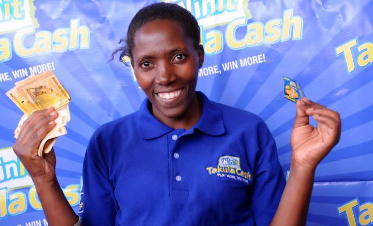 Jalia Tugumisirize shows off her winning ticket and cash.