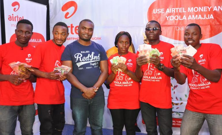 Airtel Money Commercial Manager, Moris Seguya (C) poses for a photo with winners in the 7th Airtel Yoola Amajja weekly draw
