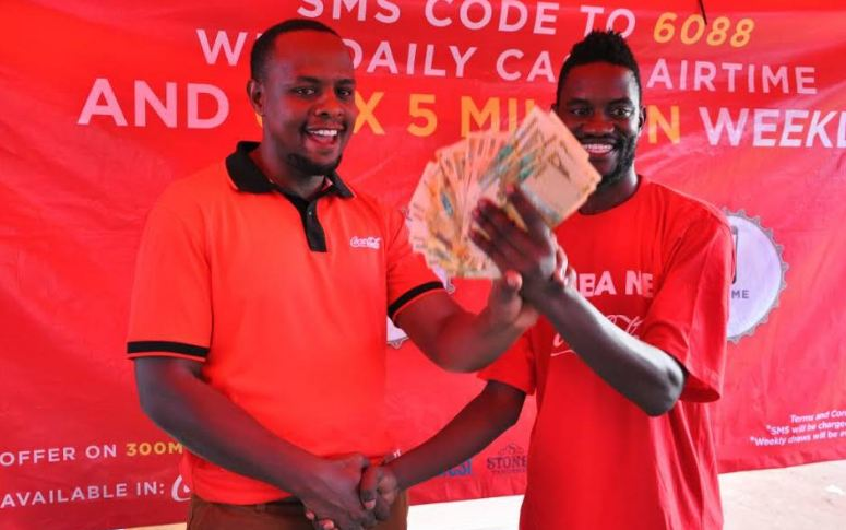 Paul Kasadha, a Jinja-based music producerreceives Ugx 5M from a Coca-Cola rep in Jinja.