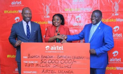 Airtel Uganda's Head of Branding and Communications, Remmie Kisakye Kakuru hands over cheque to Buganda officials.