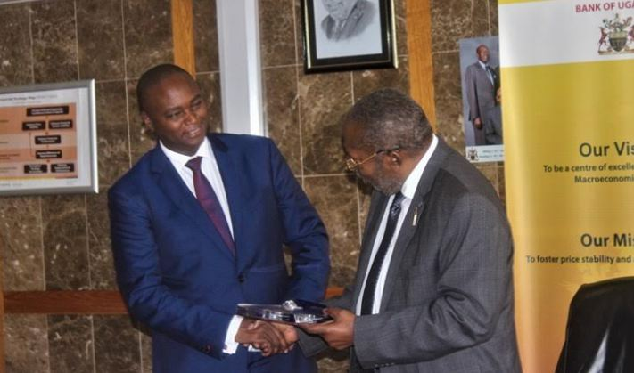 Patrick Mweheire, Chief Executive of Stanbic bank receives award of recognition for the best performing commercial bank trading in the Government securities from Governor Bank of Uganda, Emmanuel Mutebile.