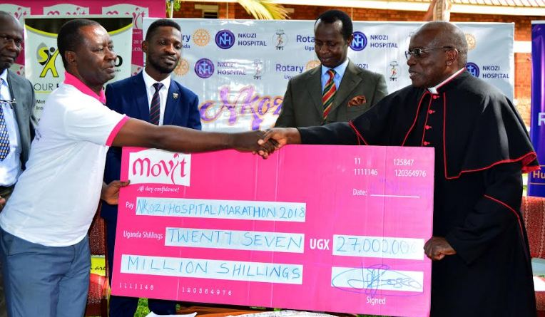 Vicar General of the Kampala archdioceses of Kampala receiving a dummy cheque from Movit's John Tumwesigye
