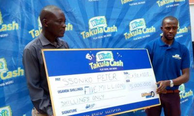 Peter Ssonko receives a dummy cheque from Takula Cash's Paul Sekantuuka.
