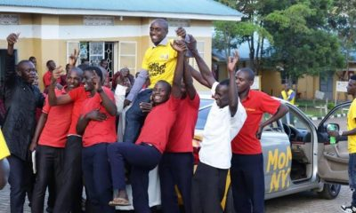 Dickens Muhereza, a bursar at Alliance Secondary School Ibanda celebrates with the school's students.