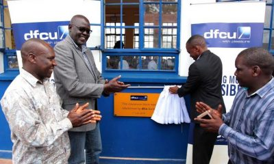 dfcu Bank's Head of Marketing, Jude Kansiime unveils the refurbished classroom block at Nakivubo Blue Primary School.
