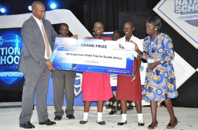 Stanbic's Patrick Mweheire hands over grand prize to Muni Girls who were overall winners.