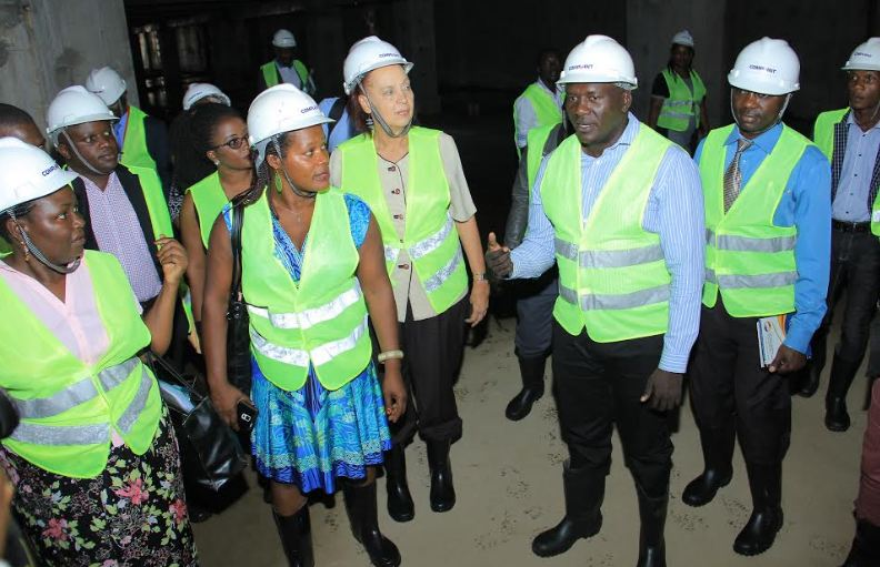 Paul Okware (3rd from right) ,NMS Chief of stores and logistics gives an explanation as he leads the Global Fund CCM team around the Kajjansi site.