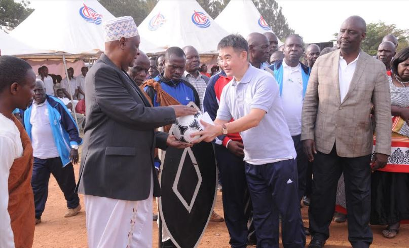 CNOOC's Cui Yujun presents a ball to the Omukama of Bunyoro Kitara Kingdom Solomon Gafabusa