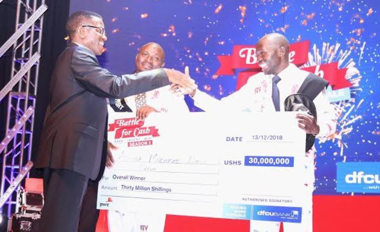 Katikiro of Buganda Owek. Charles Peter Mayiga hands over dummy cheque to the Battle for Cash Season II winners.
