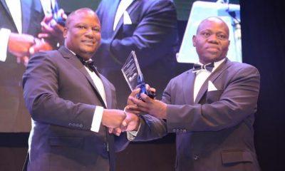 Juma Kisaame handing over a commemorative plaque to the new CEO Mathias Katamba.