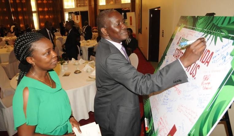 """The Permanent Secretary Ministry of Water and Environment Alfred Okot Okidi and Uganda Breweries Legal and Corporate relations director Charity Ekudu Kiyemba during the launch of the """"Running out of trees"""" campaign in October last year."""
