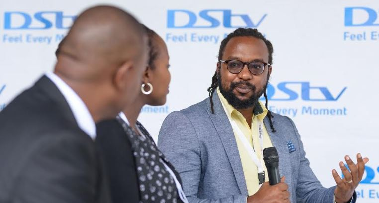 Colin Asiimwe, the Head of Marketing during the launch of Showmax at MultiChoice Uganda offices, looking on is Ms. Joan K. Semanda, the PR and Communications Manager and a staff at MultiChoice Uganda.
